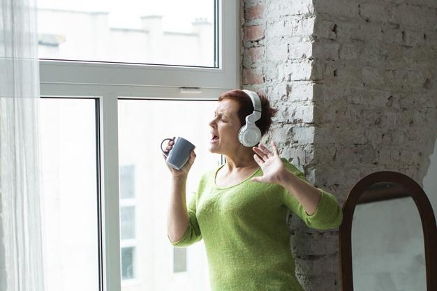 mujer escuchando musica cantando La música es felicidad y calidad de vida