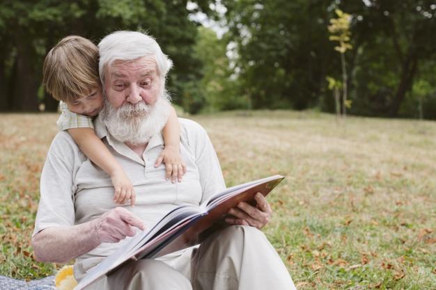 vista frontal abuelo leyendo nieto Día de los abuelos. ¿Has felicitado a los tuyos?